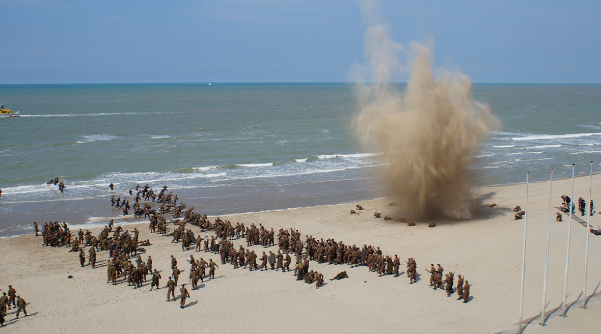 Actors dressed as WWII soldiers fight on a Dunkirk beach. A big explosion creates a cloud of sand on the beach