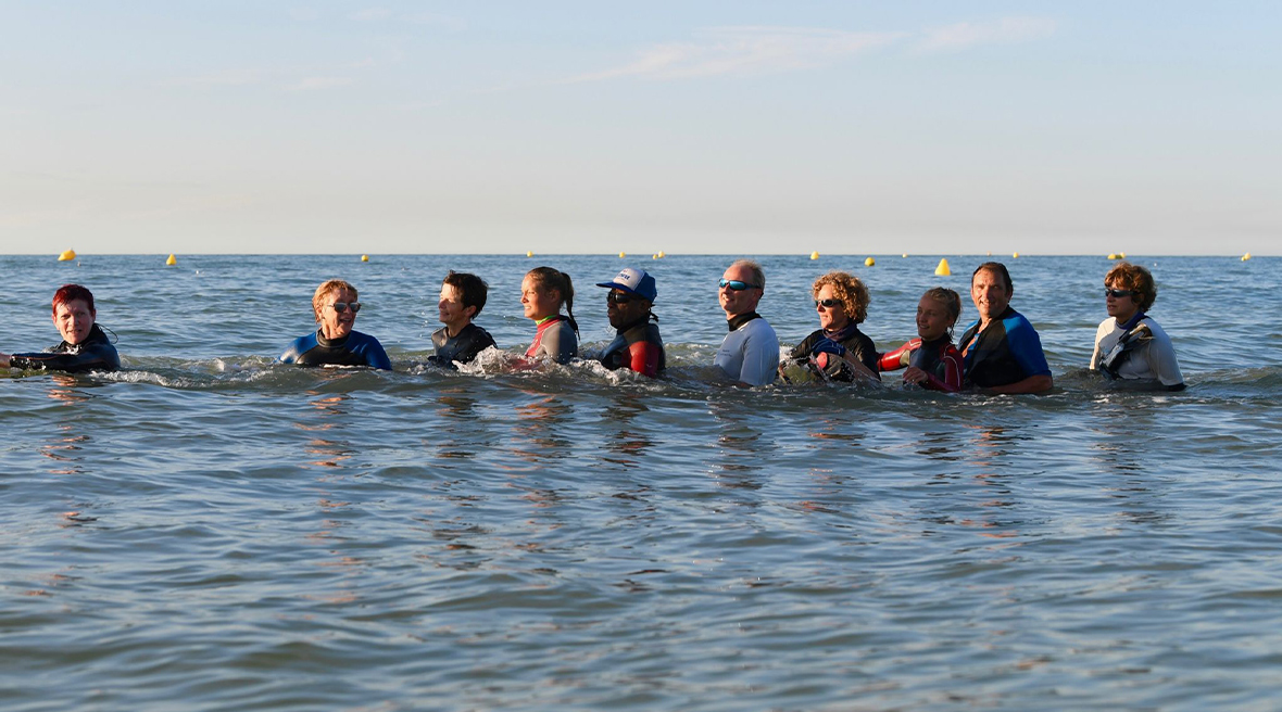A group of people walk in the sea in a group, wearing wetsuits and wading at waist depth