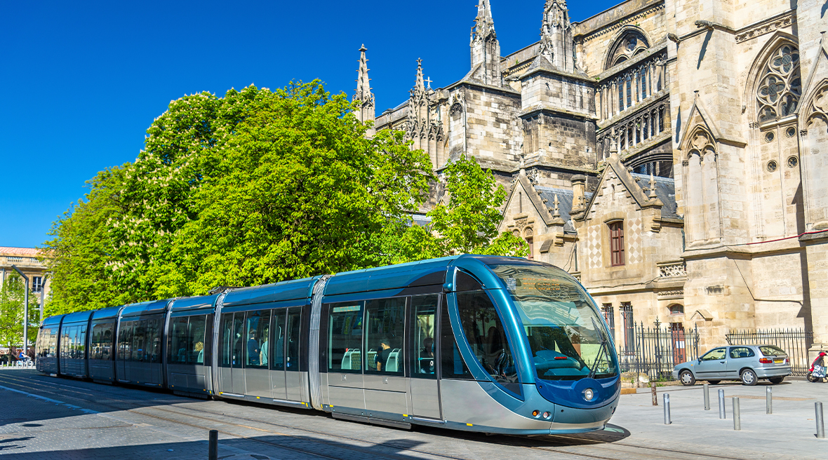 Tram pulling up outside beautiful French architecture in Bordeaux city centre