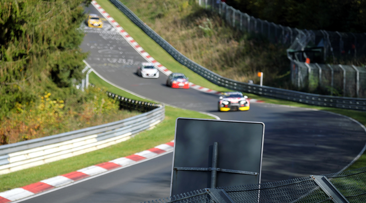 Racing cars approaching the corner on the Nürburgring track