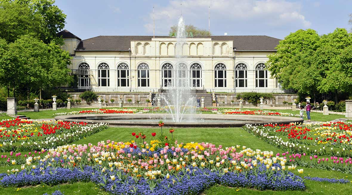 White building with green trees either side of it with green lawns and flower beds and fountain