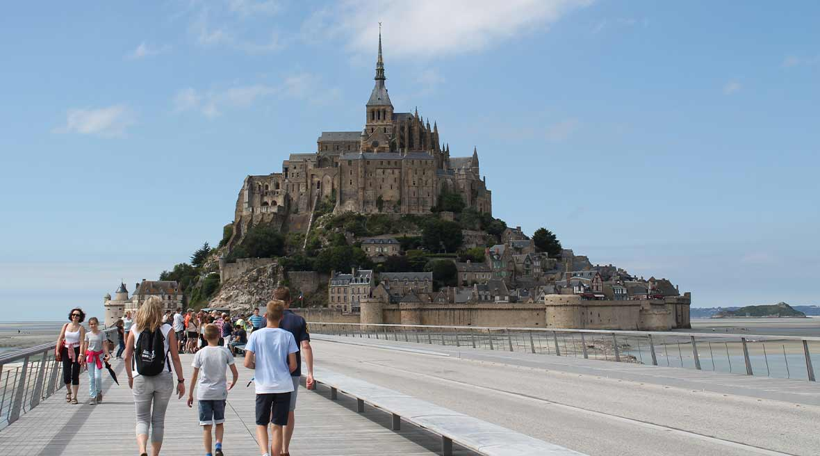 Man, woman, and boy walking along a footpath towards Mont Saint-Michel beneath a blue sky surrounded by golden sands