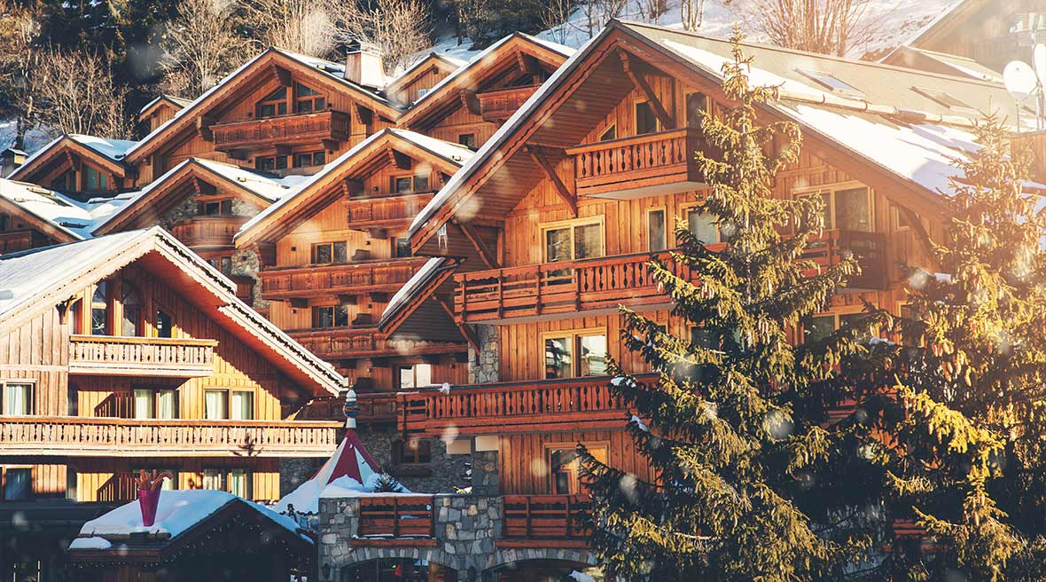 wooden chalets in the alp mountains France surrounded by snowy hills and fir trees