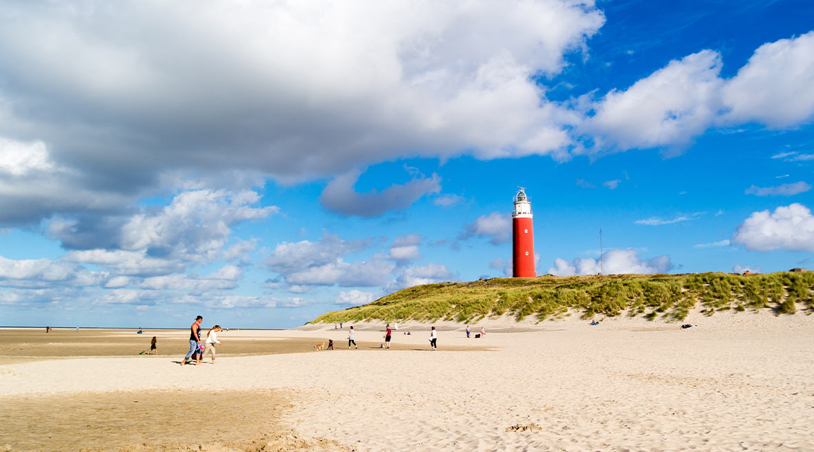 Large stretch of sand under big blue sky with a bright red lighthouse on top of a green dune