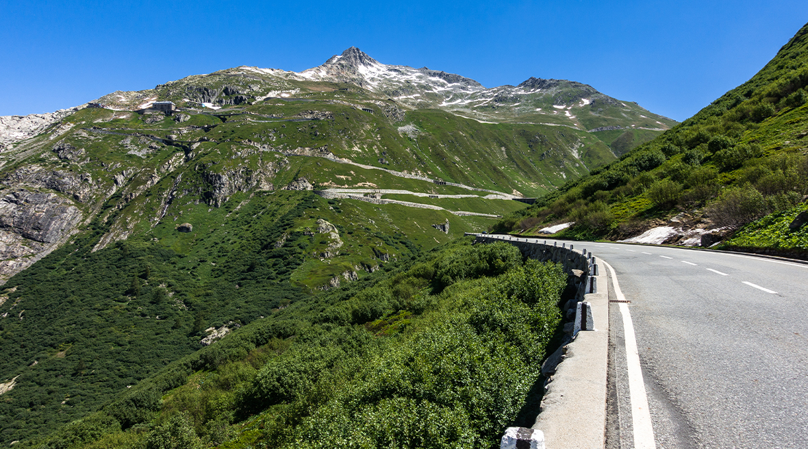 Furka pass road within the Swiss Alps surrounded by stunning greenery
