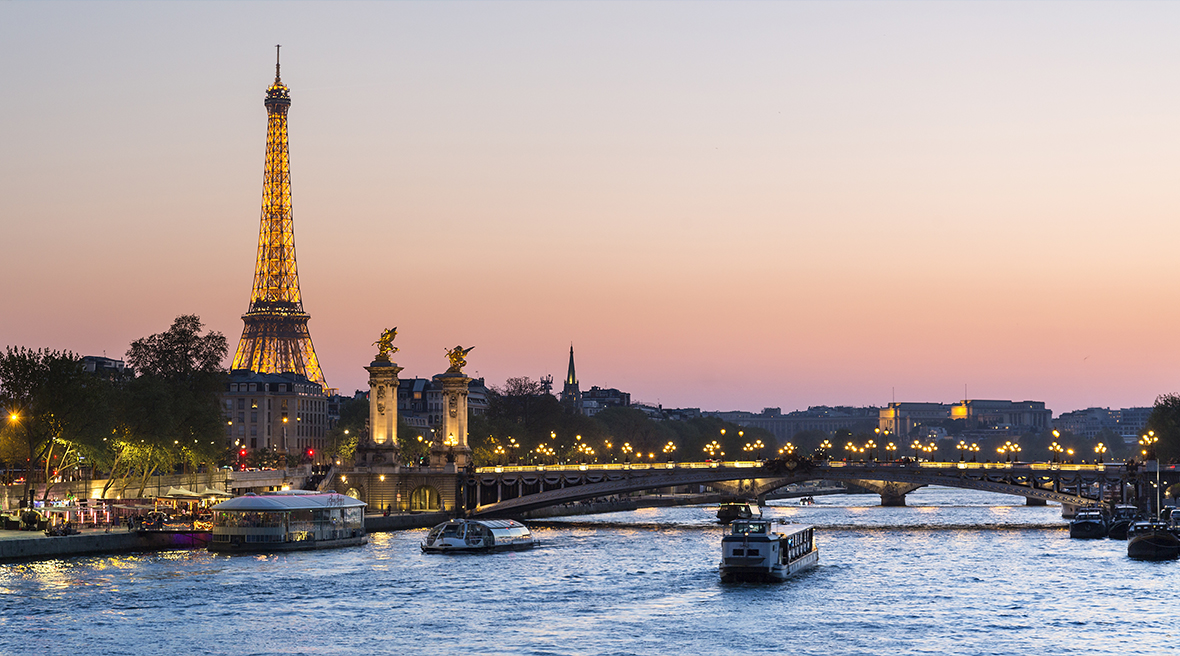 river at sunset with Eiffel Tower in the distance lit up with lights