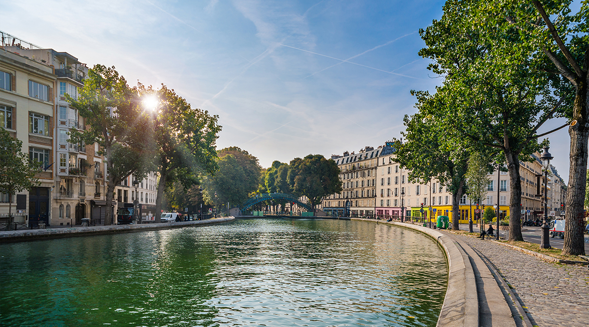 canal waters winding through French street with sunshine and leafy trees