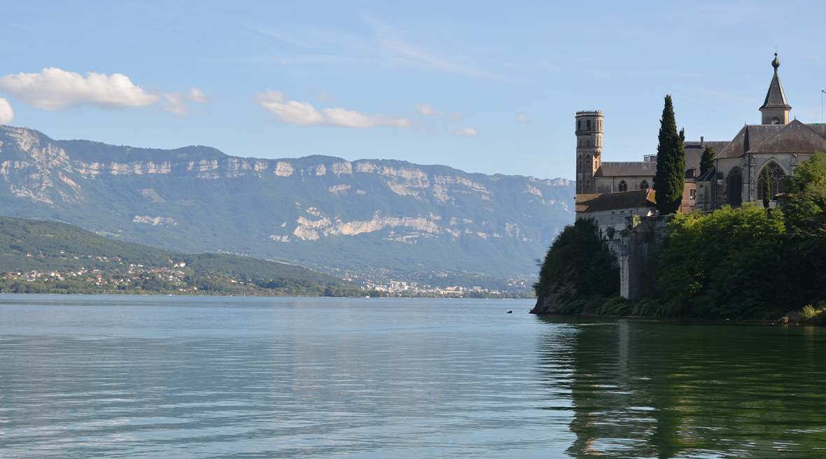 castle-like building sits on bank of still blue water with mountains in the distance