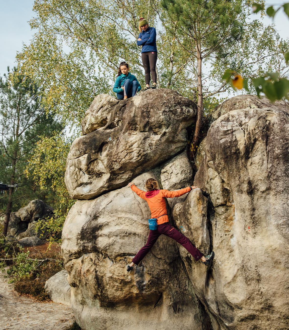 Woman  in red and orange bouldering with two friends helping her navigate the climb