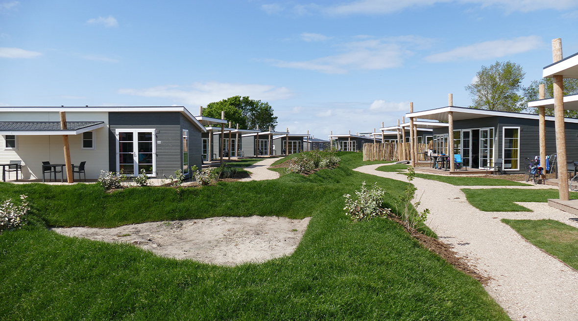 Cabins in rows, blue sky and bright green grass at Camping Nieuwpoort