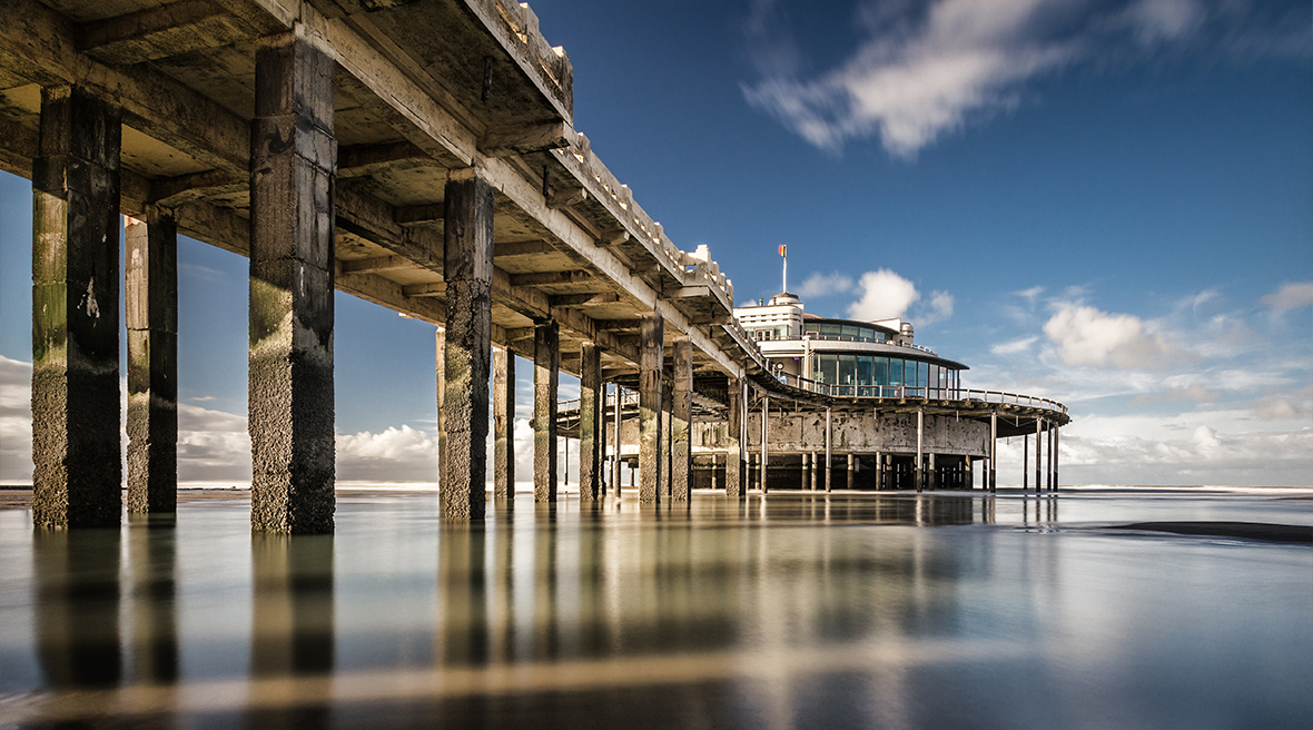 View of the pier at Blankenberge from the shore with a clear blue sky