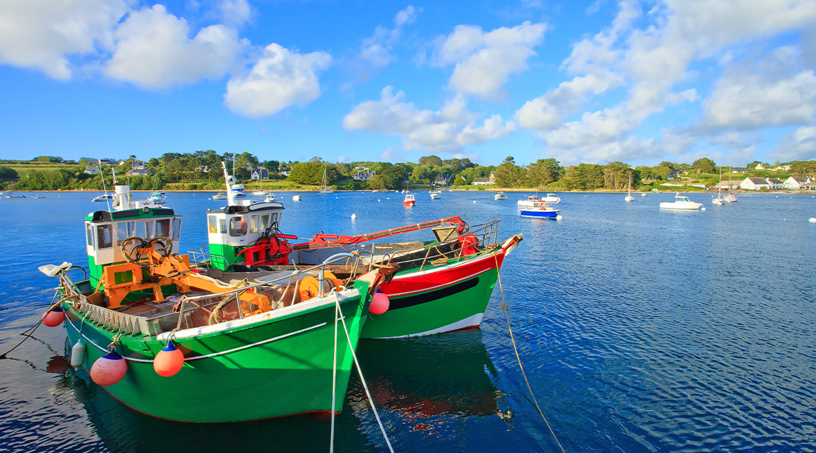 Two colourful boats on blue waters in a pretty, sunny port