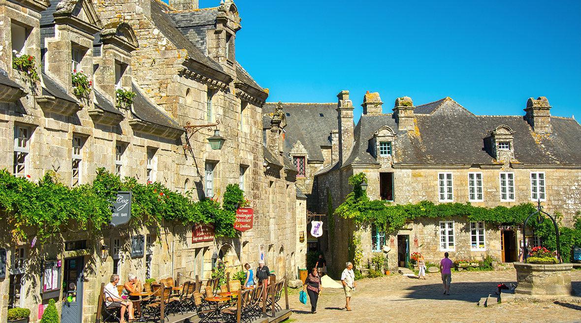 Beautiful French architecture village square with people wandering cobbles streets past shops