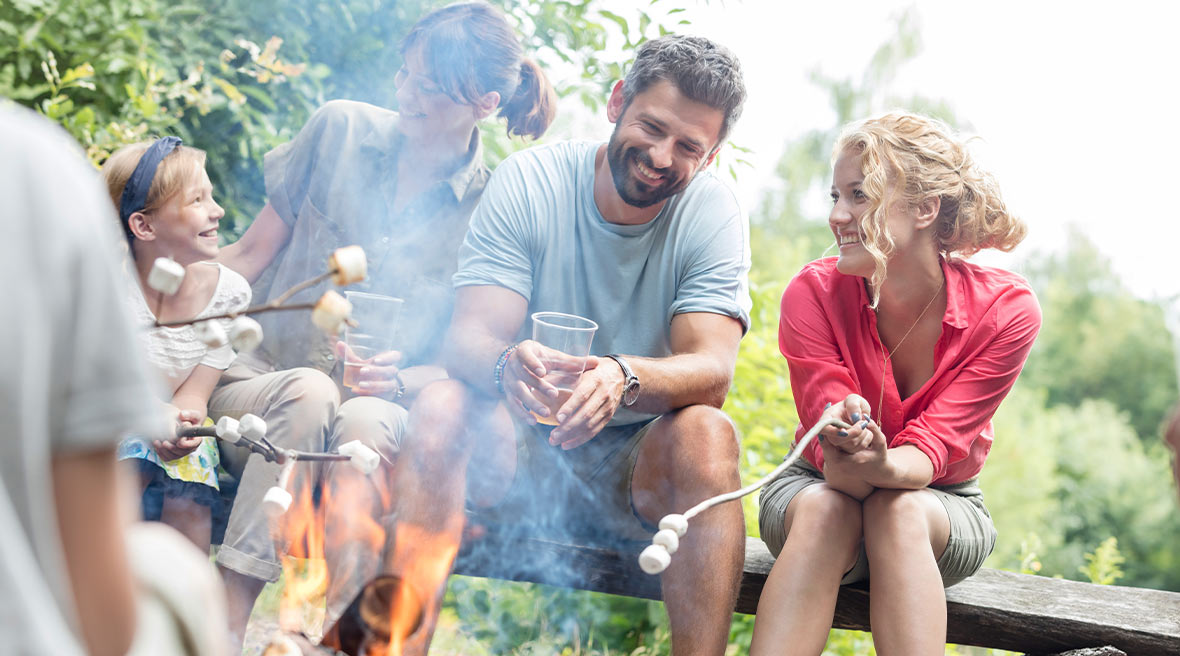 Family laughing and roasting marshmallows sitting on a log with blue sky in the background