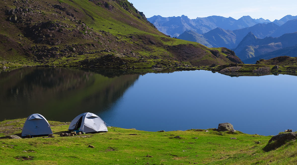two grey tents pitched by a lake surrounded by the Pyrenees mountains in a lush green park