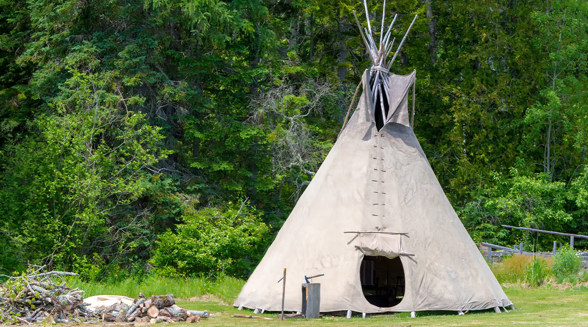 Tepee tent in a field with the door open surrounded by trees with an unlit fire to the left of it