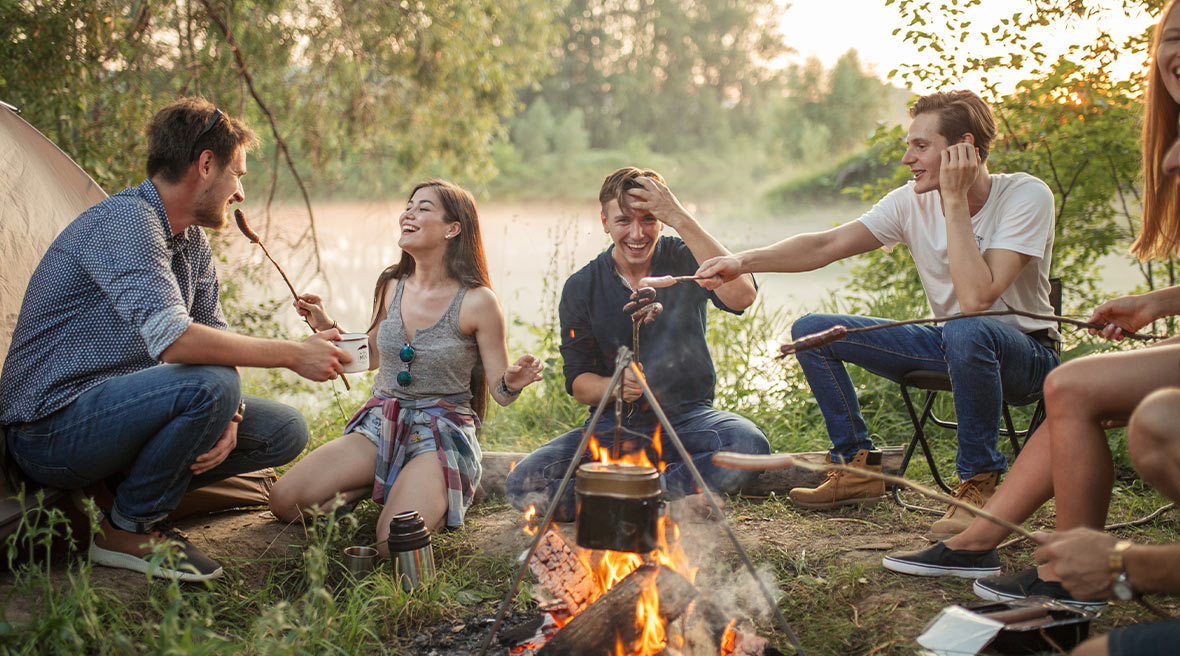 Group of five friends laughing around a campfire in a field surrounded by more trees as the sun sets