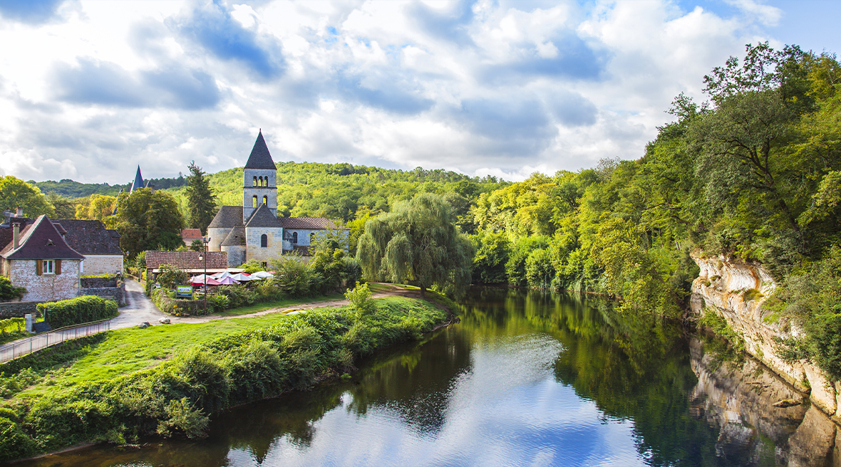 A river running past lush greenery and a small picturesque town with a turreted building