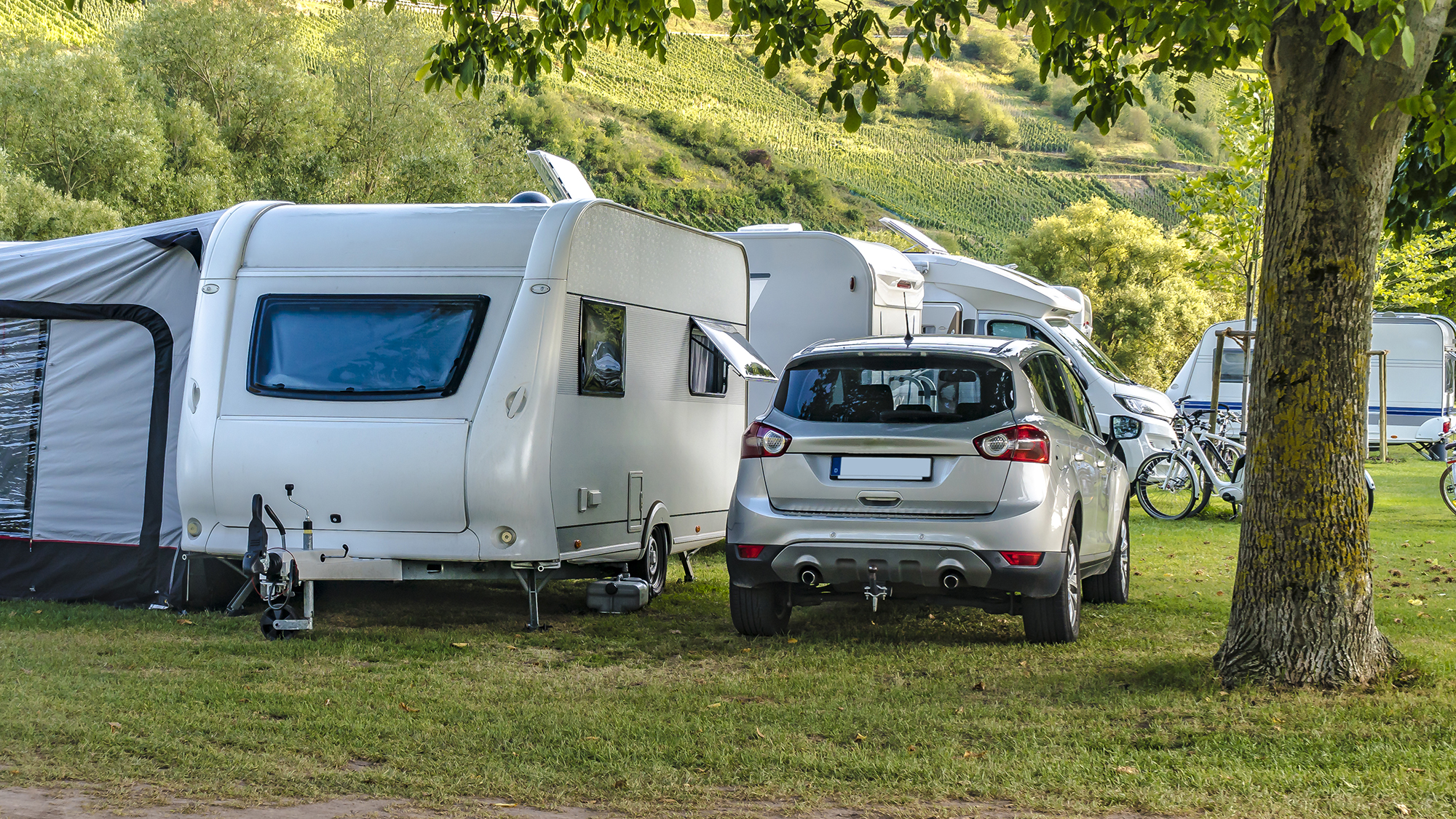Caravan with awning attached next to a car in the French countryside