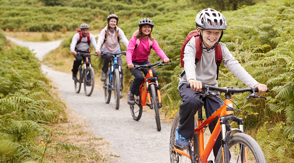 Family of four enjoying riding their bikes through a woodland trail