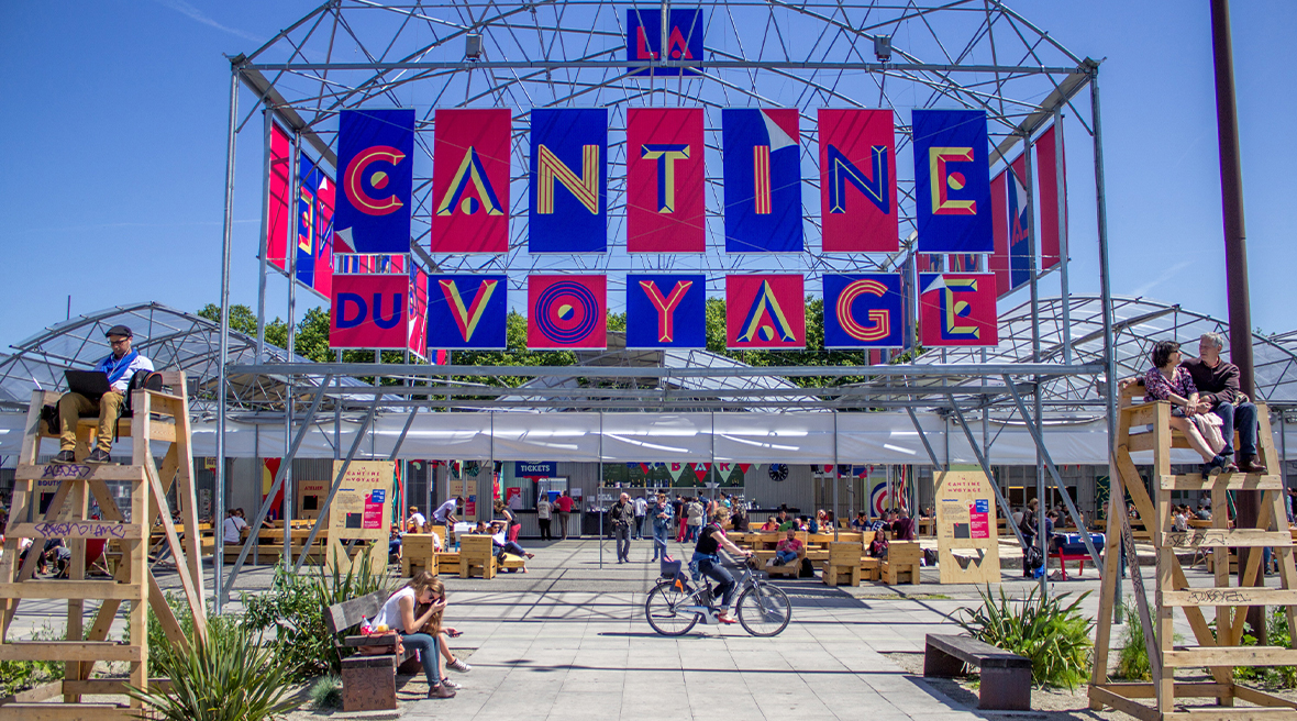 woman in bike cycling through outdoor canteen with huge colourful signage, plants, and people
