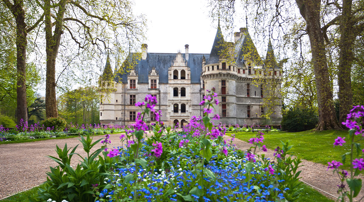 Colourful flowers in the foreground with a huge French turreted castle behind