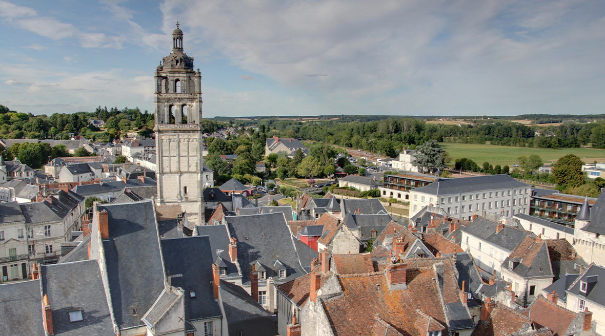 Panoramic view of an old French city with sloped rooftops and a bell tower in the distance