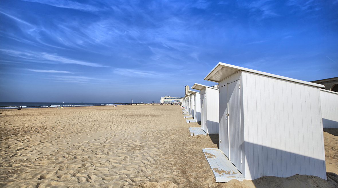 white beach huts on a long stretch of sandy beach under blue skies