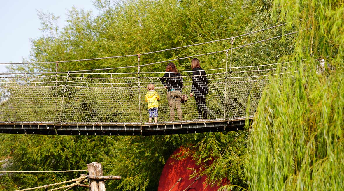 two adults and a child in a yellow coat on suspension bridge above the green park amongst the trees