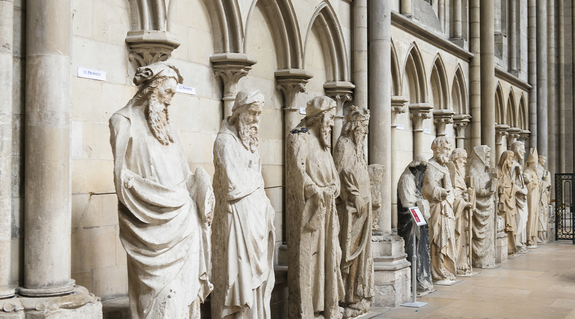 White stone statues in a Gothic style inside archways of a church