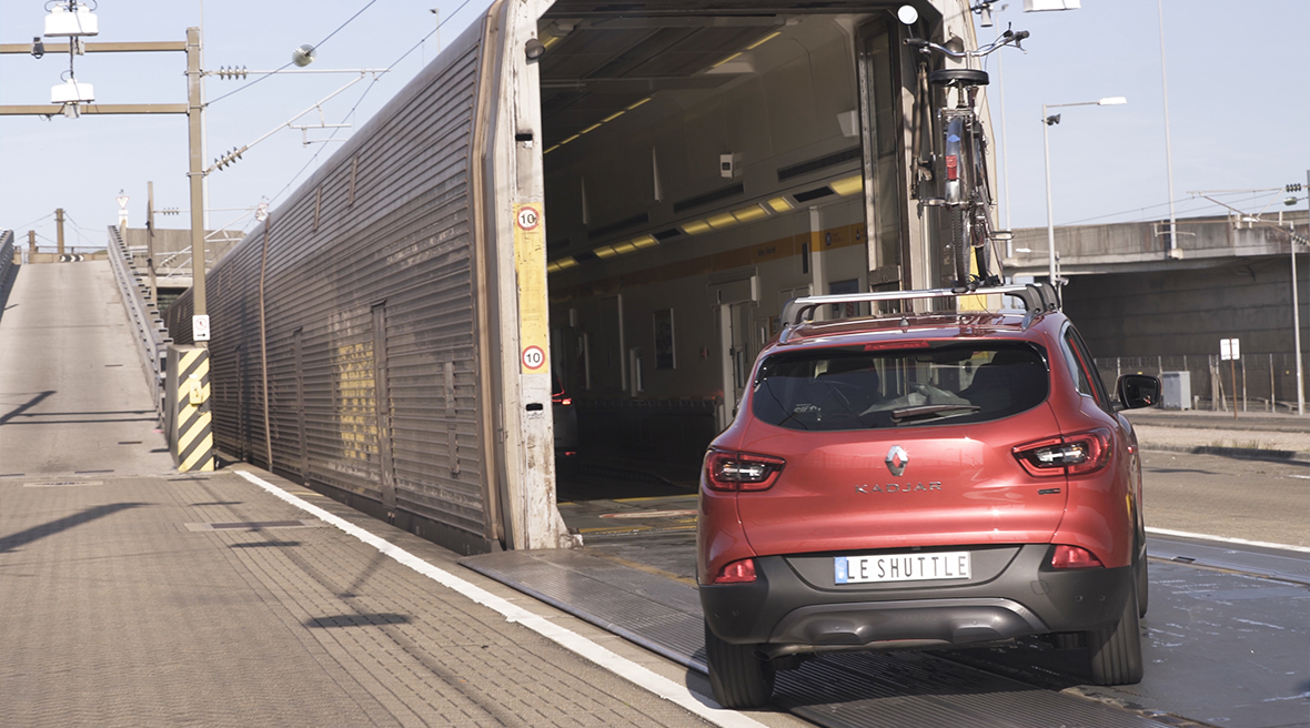 A red car driving onto a Eurotunnel Le Shuttle train from the platform