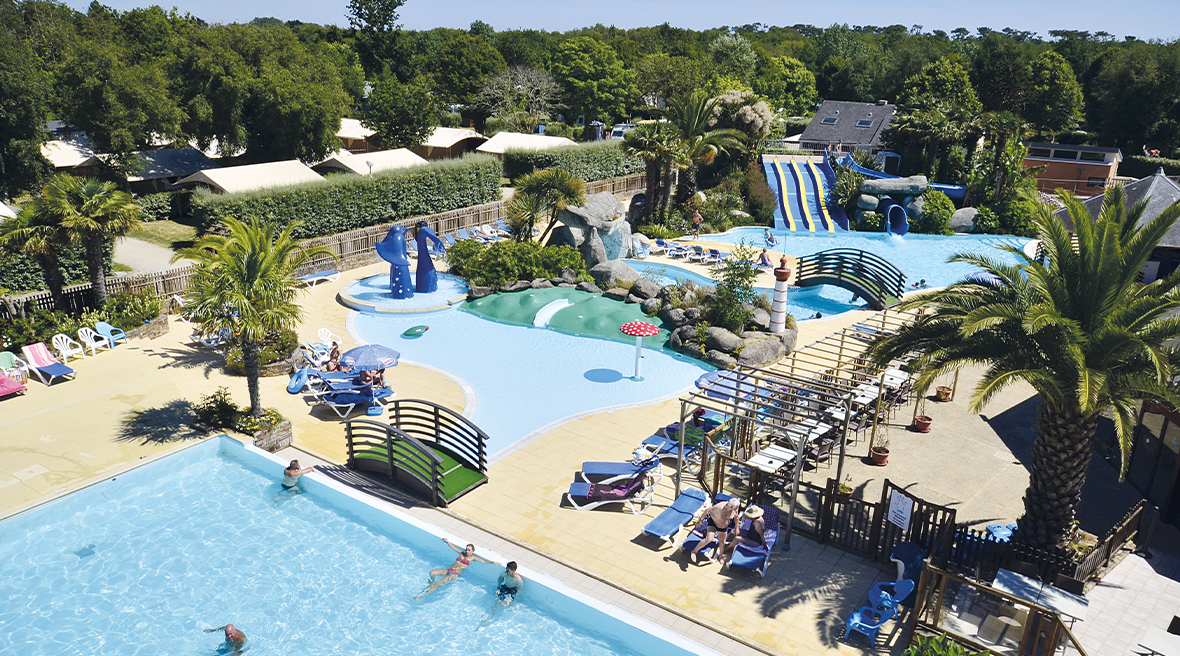 view of three swimming pools with water slides and sunbeds