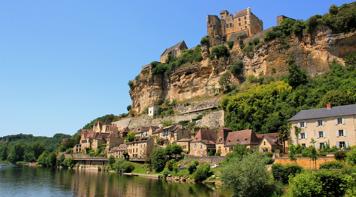 French town set into a hillside on riverbank