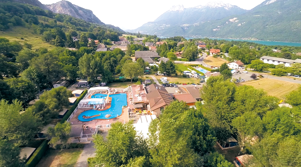 Swimming pool and lush forestry with a lake and snow-capped mountains in the background