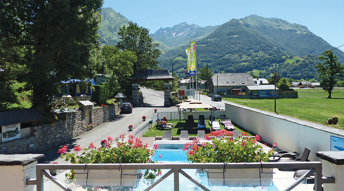 Swimming pool with mountains in background and flowers in the foreground
