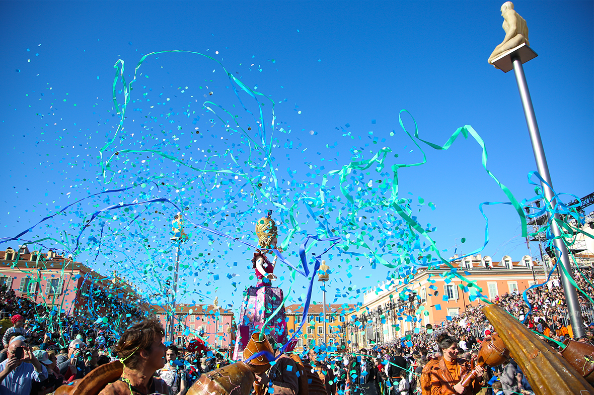 Blue confetti and ribbons shooting into the air with buildings and a crowd in the background