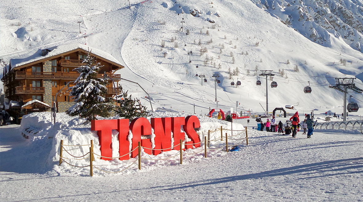 Red letters spelling Tignes in the snow outside ski centre with mountains in background
