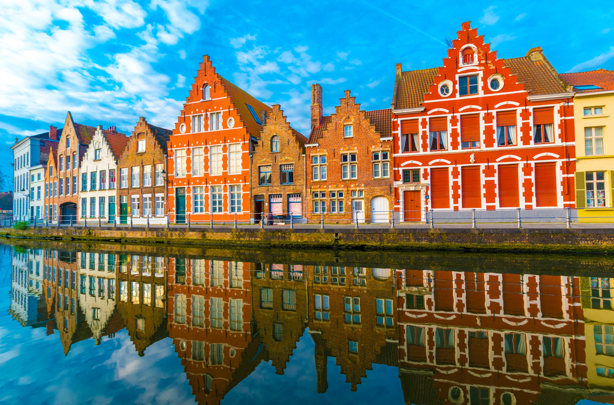 Colourful medieval buildings line a canal in Bruges and are reflected in the water