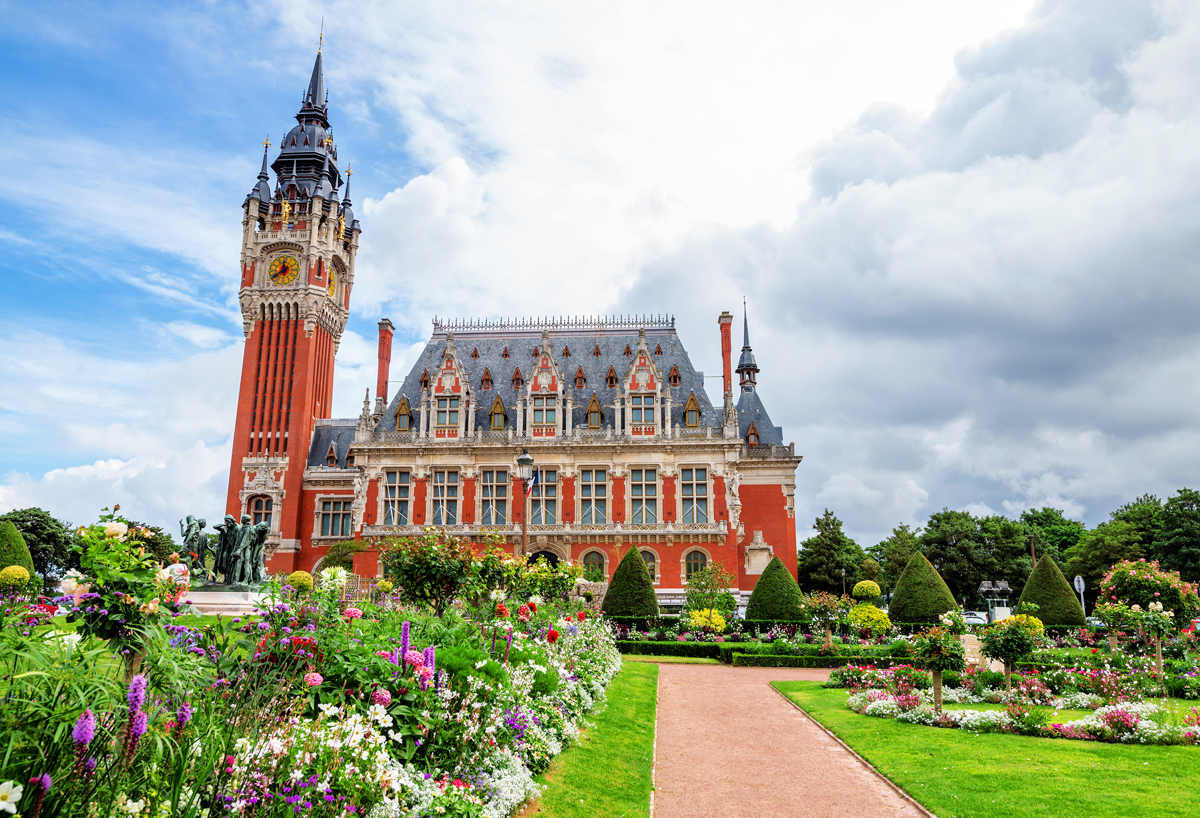 View of Calais' Hôtel de Ville set in landscaped gardens with flowers