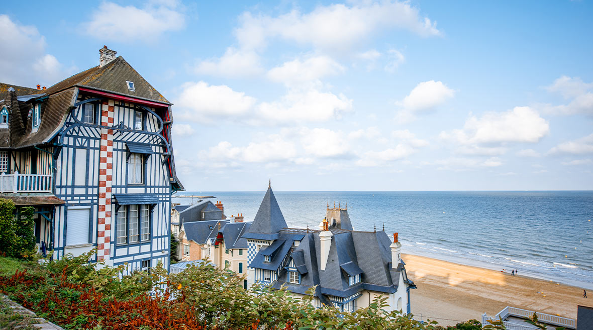 Pretty French houses with a path leading down to a sandy stretch of beach under blue skies