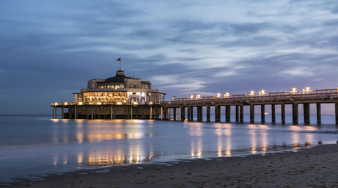 A lit up pier and building at sunrise with sand and sea in the foreground