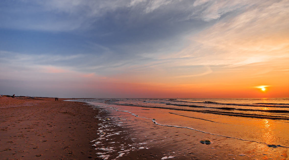 sunset on a stretch of beach with blue and orange sky