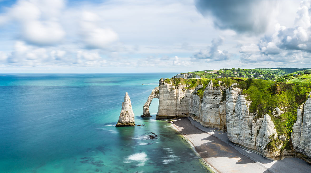View of the white cliffs of Étretat, the pebbled beach and a blue sky with white clouds