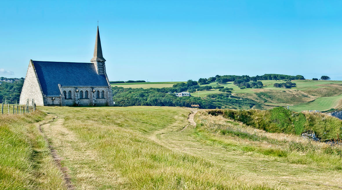 Panorama of Notre Dame de la Garde chapel and the cliff of Etretat, Normandy, France beneath a clear blue sky and surrounded by calm blue waters and grass