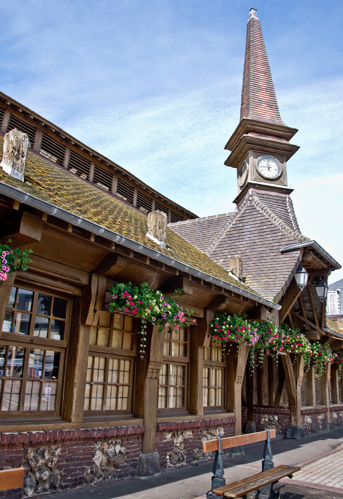 Old covered market building Etretat with clock tower and hanging floral baskets in the windows