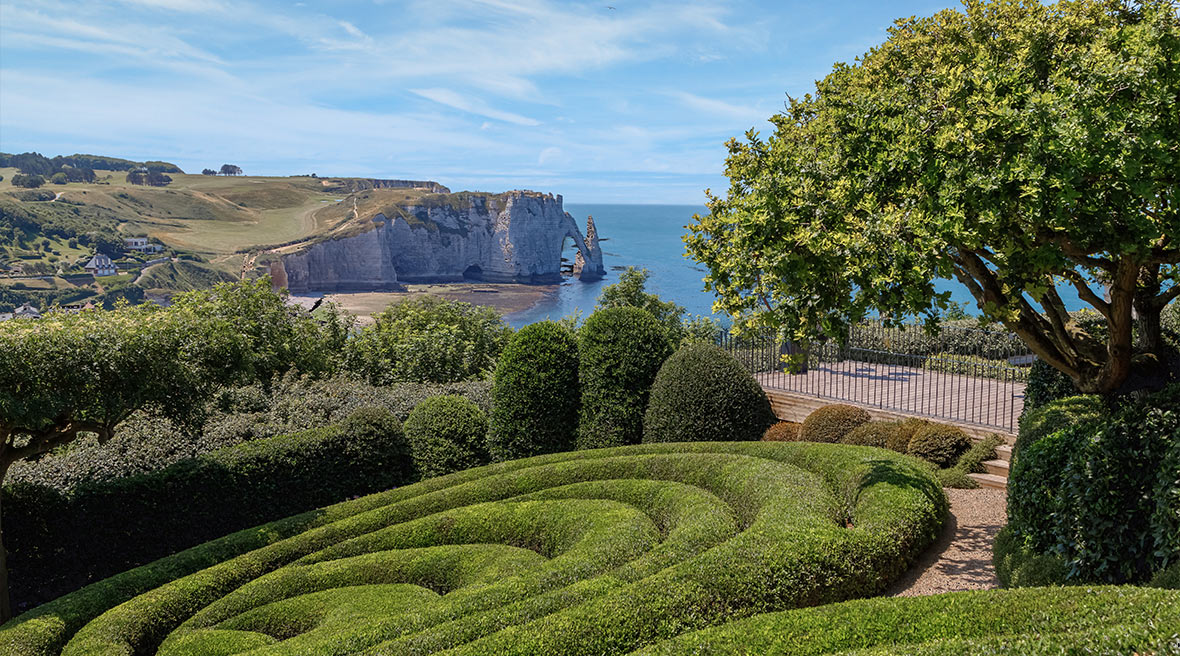 View of the famous white chalk Etretat cliffs from the garden (Jardin d'Etretat) with visible ocean stretch and swirling green hedge in the garden