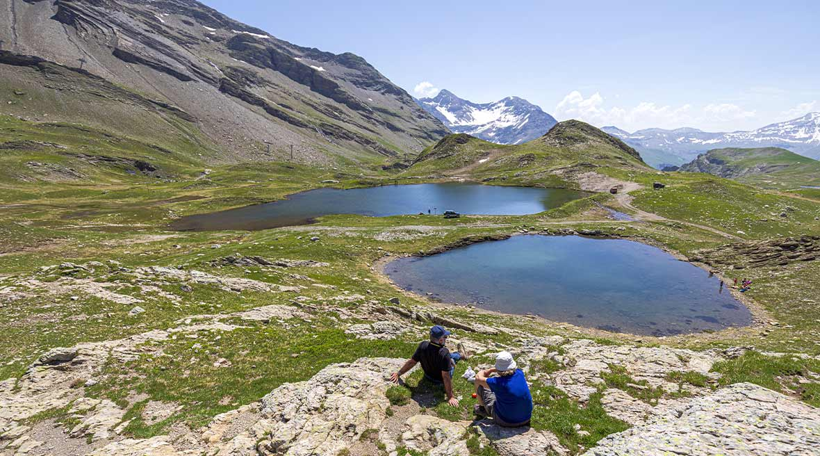 Two hikers enjoying a rest by lakes up in the snow-capped mountains