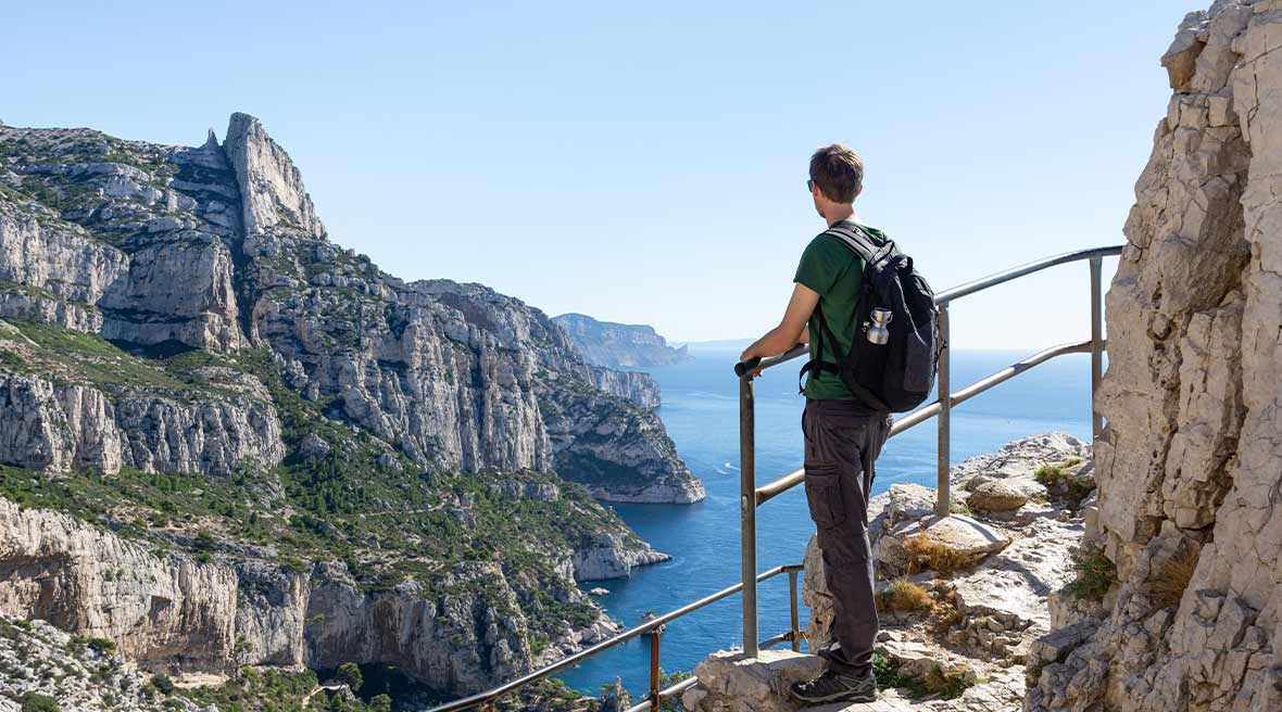 Man with backpack looking out across blue waters and white cliffs as he hikes a marked path with railings