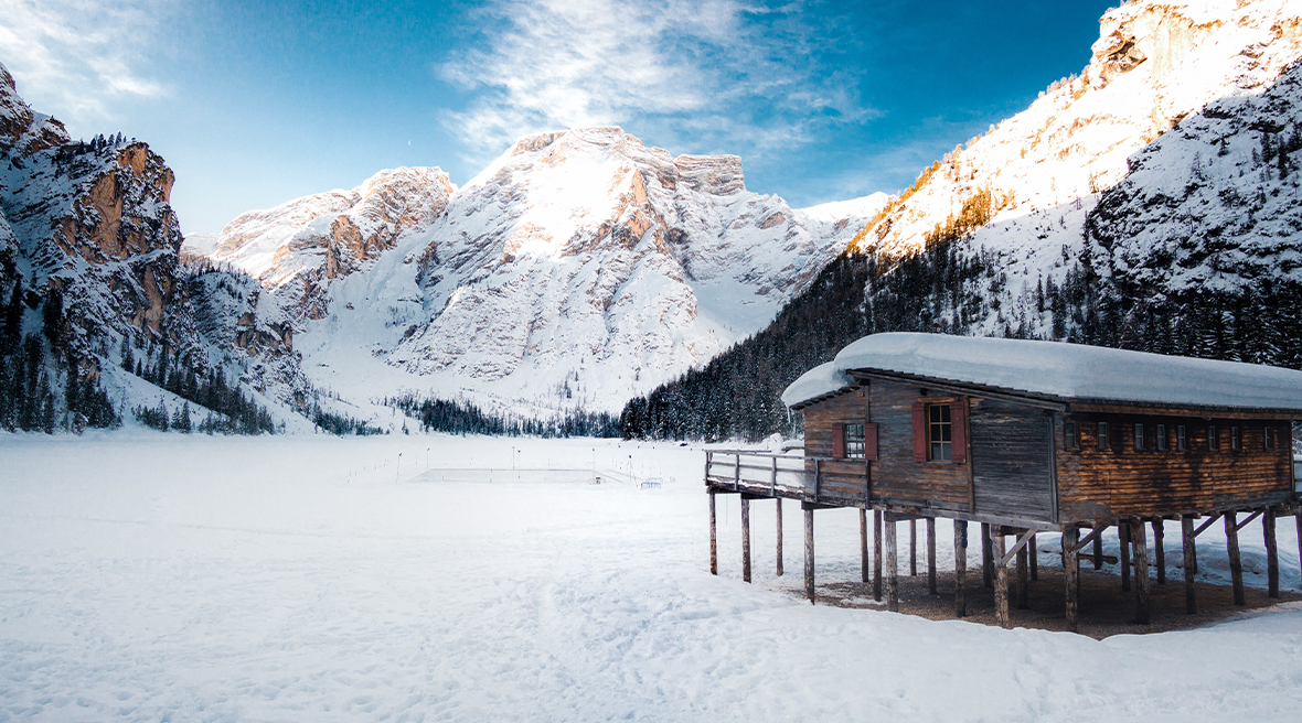 Frozen Brais Lake and cabin, overlooking the Dolomite mountains