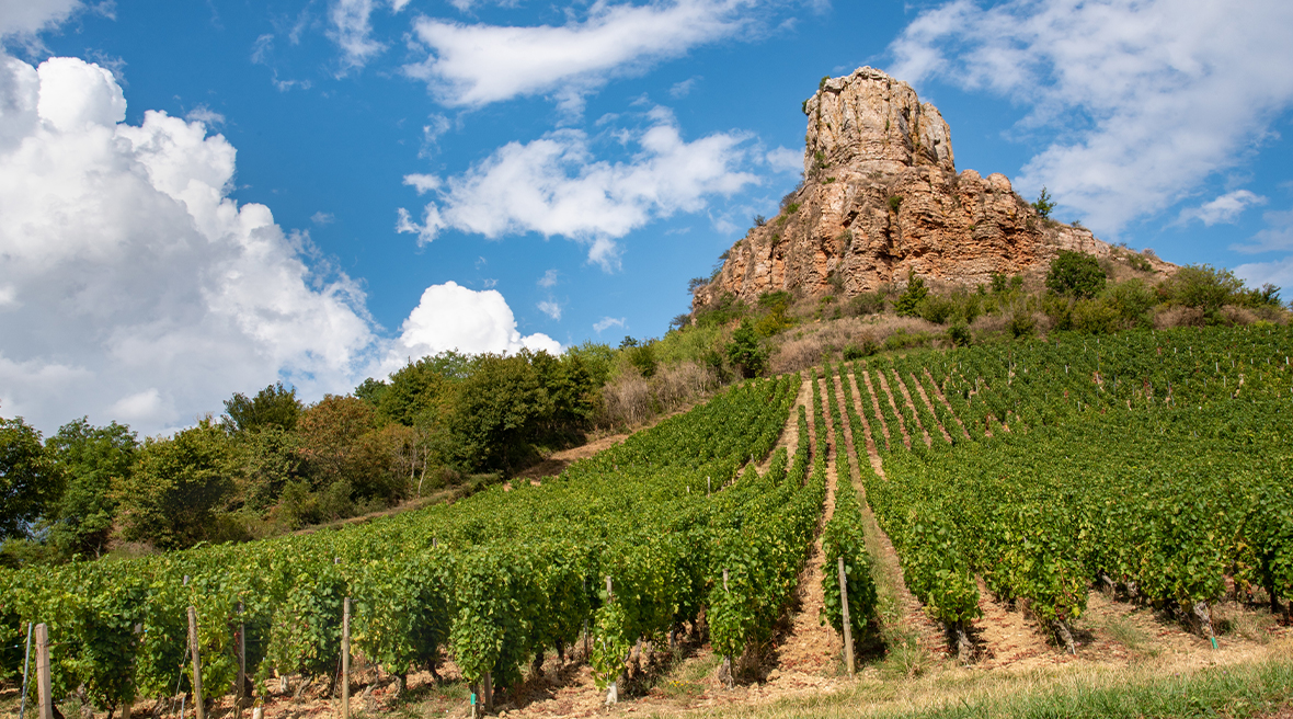 Natural rock formation above vineyard against blue skies